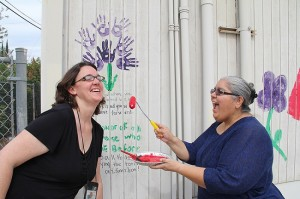 Family Resource Center Coordinator Jennifer Kottke, left, and Community Liaison Irma Almanza have fun saying goodbye to the old portable by painting on it before it is torn down.