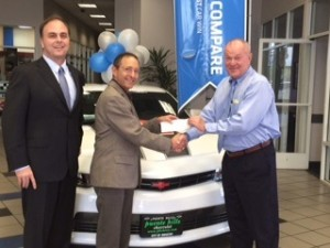 Craig Cerro of San Gabriel Valley YMCA receives a donation from  Tom Hoffman , owner Puente Hills Chevrolet.