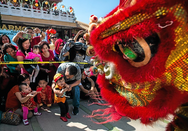 People hand money to Lion dancers at Hsi Lai Buddhist Temple in Hacienda Heights. (Photo by Watchara Phomicinda