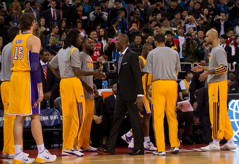 Kobe Bryant of the LA Lakers, center, greats his teammates during their NBA Global Game against Golden State Warriors at the Wukesong Stadium in Beijing, Tuesday, Oct. 15, 2013. The Warriors defeated Lakers 100-95. (AP Photo/Andy Wong)