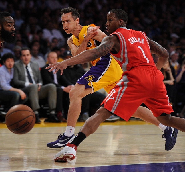 Lakers#10 Steve Nash passes the ball around Rockets#1 Isaiah Canaan in the first half. Nash would go on to become the 3rd all-time leader in assists later in the first half. The Houston Rockets traveled to Los Angeles to play the Lakers in a regular season game at Staples Center. Los Angeles, CA. April 8, 2014 (Photo by John McCoy / Los Angeles Daily News)