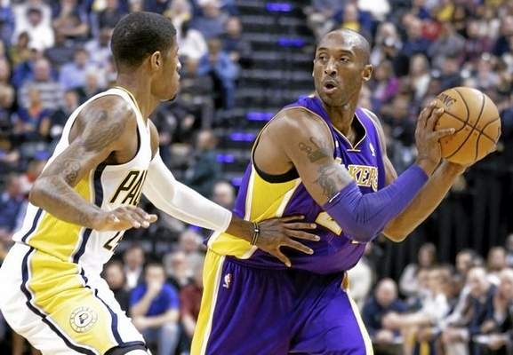 Los Angeles Lakers guard Kobe Bryant, right, looks to pass around Indiana Pacers forward Paul George in an NBA basketball game in March 2013.  Bryant played only six games last season. (AP Photo/Michael Conroy)