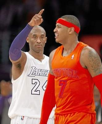 In this file photo, Kobe Bryant of the Los Angeles Lakers gestures beside a grimacing Carmelo Anthony of the New York Knicks in the fourth quarter of their NBA game at Staples Center in Los Angeles on Dec. 25, 2012. The Lakers defeated the Knicks 100-94. Now, Anthony is a free agent and the Lakers will meet with him to see if he has a potential future with the West Coast team. (ROBYN BECK/AFP/Getty Images file)