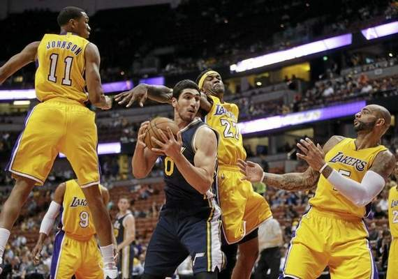 Utah Jazz's Enes Kanter, center left, gets a rebound against Los Angeles Lakers' Jordan Hill as Lakers' Wesley Johnson, left, and Carlos Boozer watch during the first half of a preseason NBA basketball game Thursday, Oct. 16, 2014, in Anaheim, Calif. (AP Photo/Jae C. Hong)