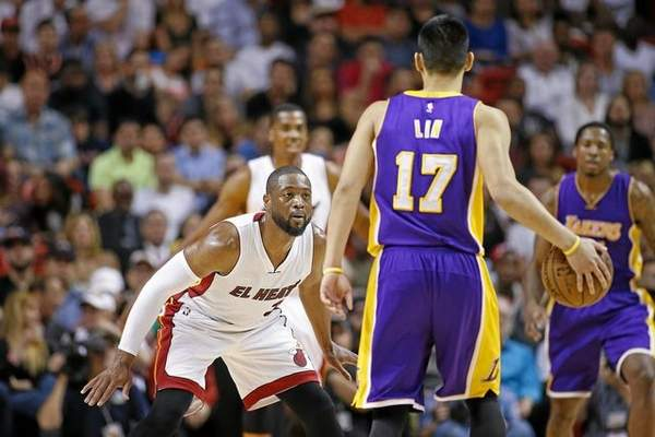 Miami Heat's Dwyane Wade (3) defends against Los Angeles Lakers' Jeremy Lin (17) as he brings the ball up court during the second half of an NBA basketball game in Miami, Wednesday, March 4, 2015. The Heat defeated the Lakers 100-94. (AP Photo/Joel Auerbach)