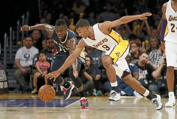 New Orleans Pelicans' Jrue Holiday, left, and Los Angeles Lakers' Ronnie Price, right, reach for a loose ball during the second half of an NBA basketball game Sunday, Dec. 7, 2014, in Los Angeles. The Pelicans won 104-87. (AP Photo/Danny Moloshok)