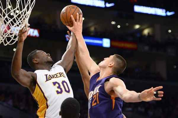 The Lakers' Julius Randle, left, rejects a shot by Alex Len of the Suns during Sunday night's game at Staples Center. David Crane – staff photographer