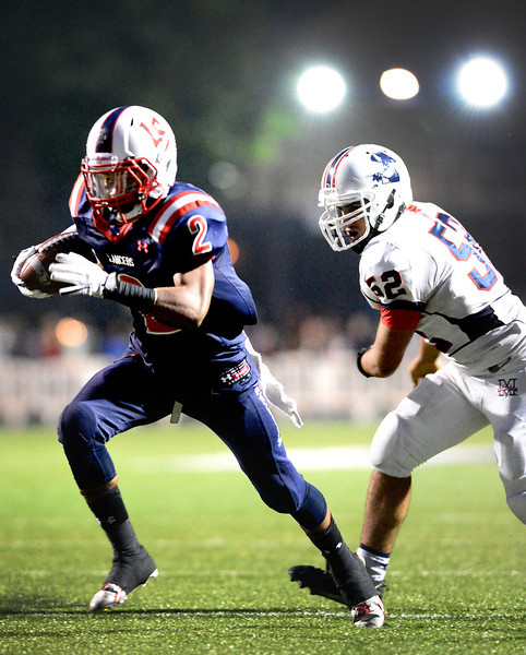 Maranatha's Chris Ajalat (52) attempts to stop La Salle's running back Bryce Harvey (2) as he makes a touchdown during the first half of Friday night's prep football game at La Salle High School in Pasadena, on September 20, 2013.  (Photo by Sarah Reingewirtz/Pasadena Star-News)