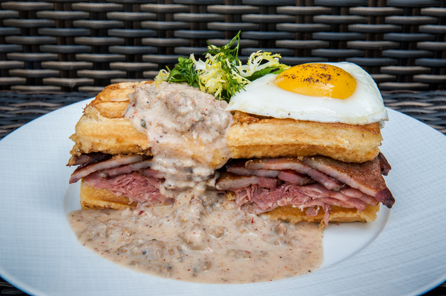 The Three Little Piggies breakfast sandwich, served at the Little Nell hotel's Element 47 restaurant in Aspen, consists of a quarter-pound of slow-roasted shaved porchetta, smoked and pan-seared pork belly and house-made sausage gravy, resting on top of an egg-battered French toast waffle, topped off with a fried farm egg. (Photo via Associated Press)