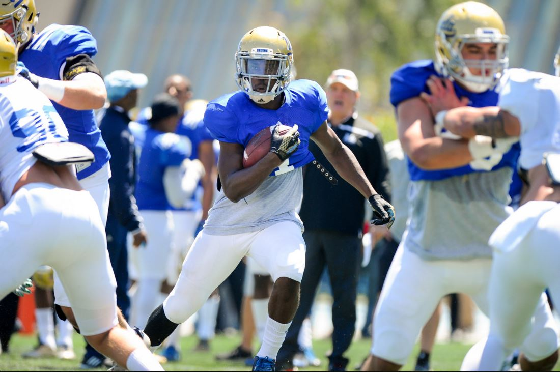 Running back Soso Jamabo bursts through the line during UCLA's Spring Showcase. Photo by Michael Owen Baker