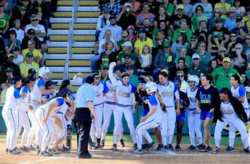 UCLA players and team members gather around home plate as the team celebrates the tying run in the bottom of the seventh inning to force extra innings against Oregon in the first game of the day in the NCAA softball tournament super regional Sunday, May 29, 2016, in Eugene, Ore. (Collin Andrew/The Register-Guard via AP)